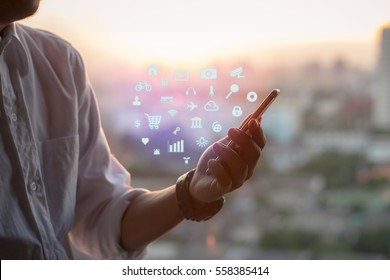 Mobile application concept.Man using touch screen smart phone on blurred urban city background,sunset