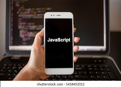 Mobile application development, Javascript programming language for mobile development. Smartphone in hand with the inscription Javascript on the screen