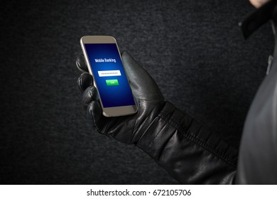 Mobile banking hack and cyber security concept. Hacker and criminal login to persons online bank application and steal money from account with smartphone. Thief with black leather gloves.