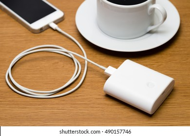 Mobile battery connected to smart phone. The charger is charging up the mobile phone on the wooden table where there is a cup of coffee.