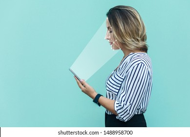 Mobile biometric identification and verification face detection concept. face ID scaning or unlocking technology. blonde woman standing and scanning face with facial recognition system on smartphone.