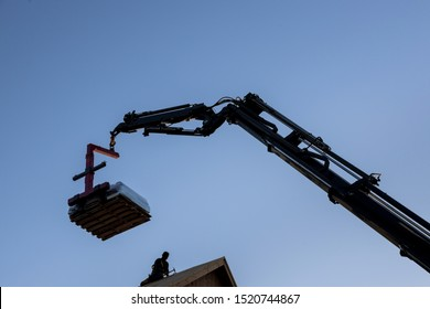 Mobile boom truck forklift delivering materials to rooftop preparing to raise construction parts