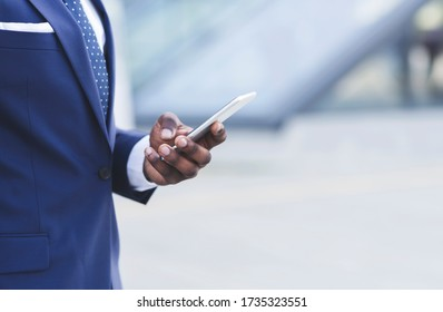 Mobile Business App. Unrecognizable Black Entrepreneur Using Phone Standing Outdoors In City. Cropped, Selective Focus