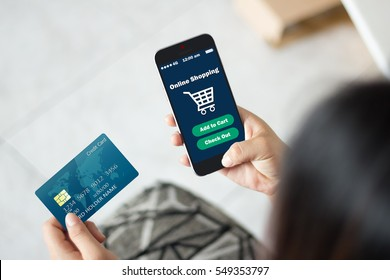 mobile business concept: Female hands using credit card and smart phone for online shopping