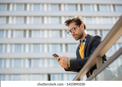 Mobile businessman in eyeglasses and smart casual reading notification in his smartphone while leaning by banisters in urban environment