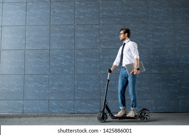 Mobile businessman with folded laptop moving on scooter along blue wall of modern building while hurrying for work