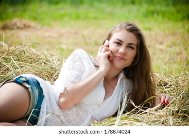 Mobile cell phone & young beautiful woman lying on hay dry grass on summer day