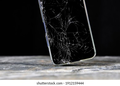 Mobile cellphone with broken glass. Smartphone falling down on the ground and broke touchscreen with beauty dark background