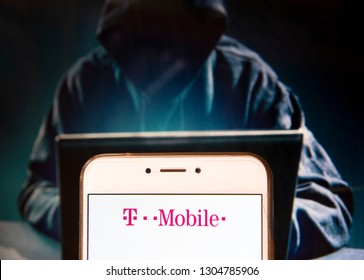 Mobile communications subsidiaries of the German telecommunications company Deutsche Telekom AG, T-Mobile, logo is seen on an Android mobile device with a figure of hacker in the background.