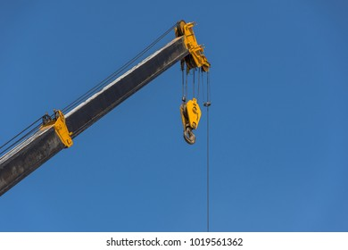 Mobile crane boom with hook hanging by wire cable background blue sky.