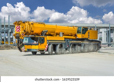 Mobile crane with cloudy sky.