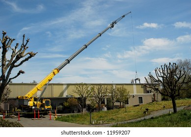 Mobile Crane delivering materials to rooftop