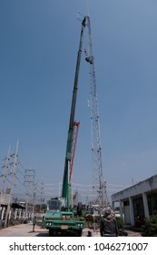 Mobile crane lifting communication tower in construction site with blue sky.