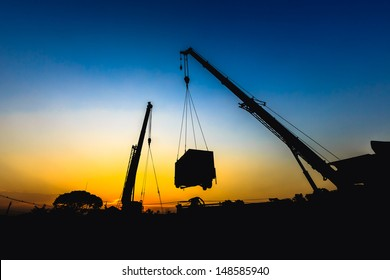 mobile crane lifting generator, silhouettes at sunset