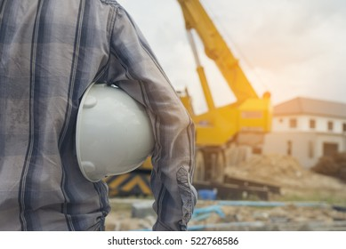 Mobile crane machine and equipment for building home is background.Young engineer or construction worker holding white safety hat (helmet) In construction plant and wearing a striped shirt scott