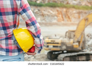 Mobile crane machine and equipment for construction site(stone quarry) is background.Young engineer or construction worker holding safety hat (helmet) and portable radio and wear striped shirt scott