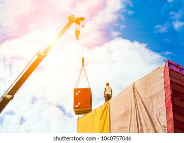 Mobile crane on a background of sky. Load on the hook of the crane. A man builder in a helmet takes a load on the roof of the building.