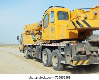 Mobile crane travels along a dusty dirt road.