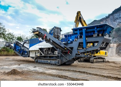 Mobile crusher and Excavator waiting for maintenance.