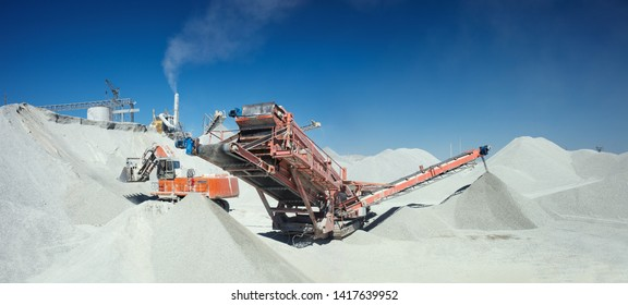 Mobile crusher machine and excavator on the background of crushed stone hills and blue sky, panorama.