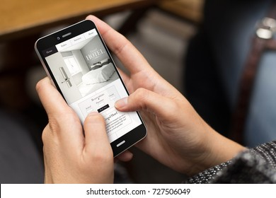 mobile design concept: girl using a digital generated phone with hotel website on the screen. All screen graphics are made up.