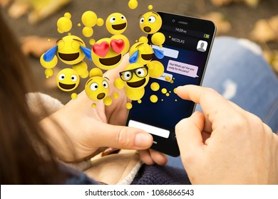 mobile design concept: woman holding a 3d generated smartphone and sending emoticons. Graphics on screen are made up.