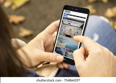 mobile design concept: woman holding a 3d generated smartphone with trends magazine blog on the screen. Graphics on screen are made up.