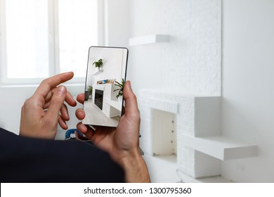 Mobile device with man hands taking picture in tiled bathroom with windows towards garden