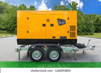 Mobile diesel charge generator for emergency electric power standing outside against green trees and blue sky