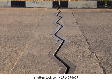 Mobile drainage connection on the carriageway of the bridge. Metallic zigzag edge of drainage channel on asphalt.