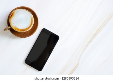 Mobile with empty screen with latte coffee cup on white marble table with free copy space. Business and technology.