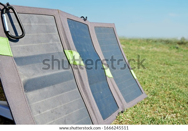 Mobile folding camping solar panel with a carbine outdoor close-up. Blue sky and green grass background.