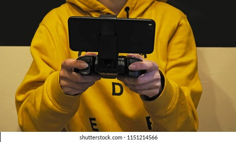 Mobile Game Pad with Smartphone in hands. Girl playing phone game.Smartphone gaming.