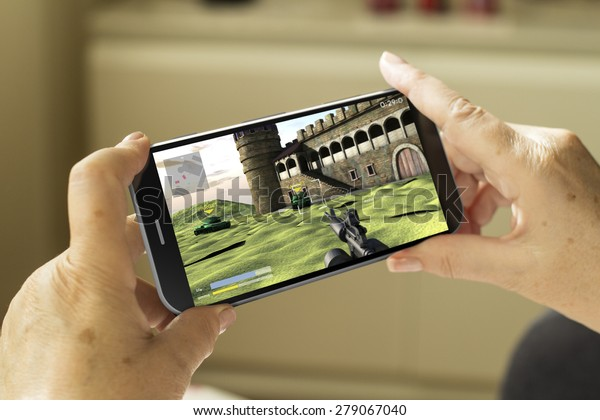 mobile gaming concept: mature woman hands with a 3d generated smartphone with game on screen