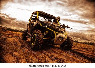 Mobile group of army rangers, state border guard service soldiers, armed commandos team moving and patrolling sandy territory on fast attack sandrail vehicle in twilight. Modern infantry light carrier