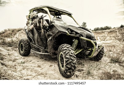 Mobile group of special operations forces, military patrol, quick reaction fighting team moving on light desert vehicle in sandy area. Modern army speed off road vehicle, combat buggy on battlefield