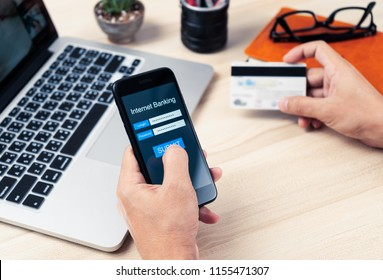 Mobile Internet Banking concept, hands holding using smart phone with personal user name and password for account log-on on screen and credit card