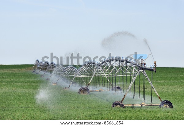 Mobile irrigation machine in action spraying water on crops