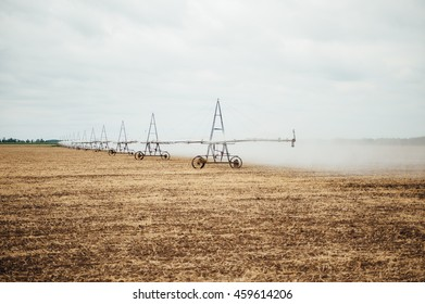 Mobile irrigation pivot watering on an empty field. Farmer watering the field after a successful harvest on a cloudy day