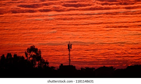 A mobile network tower of a city with red cloudy sky unique photo