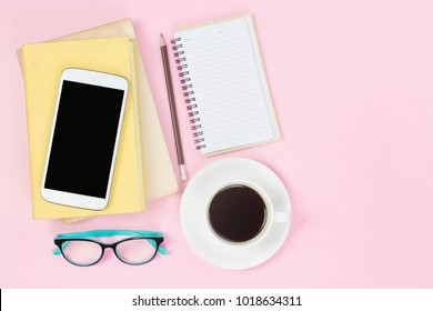 Mobile on old two books and notebook pencil glasses black coffee white cup on pink background copyspace flatlay pastel style