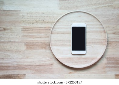 mobile on the wood plate and wood table on top view,concept