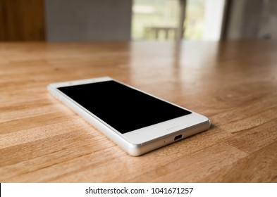 mobile on wooden desk with nobody in the room