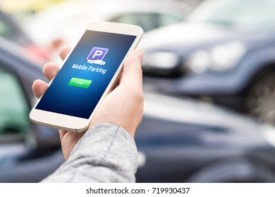 Mobile parking app on smartphone screen. Man holding smart phone with car park application in hand. Internet payment online with modern device.