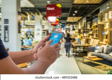 Mobile payment, Cashless society concept. Hand holding smart phone with mobile payment on screen  and NFC signals icons against abstract furniture mart background.