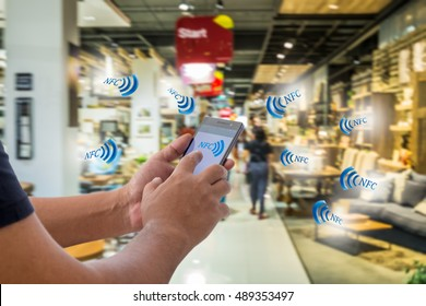 Mobile payment, Cashless society concept. Hand holding smart phone with NFC icon on screen  and NFC signals icons against abstract furniture mart background.