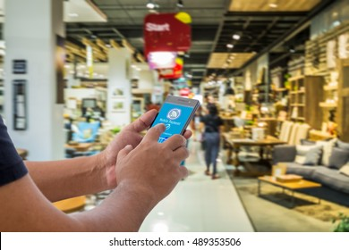 Mobile payment, Cashless society concept. Hand holding smart phone with mobile payment on screen against abstract furniture mart background.