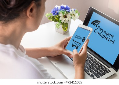 Mobile payment, Cashless society concept. Woman uses mobile payment to shopping online with laptop computer on working desk at home.