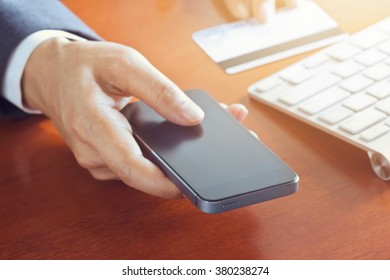 Mobile payments, business man using smartphone and credit card for online shopping, soft focus