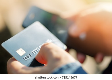 Mobile payments concept. A man holding credit debit card and making a payment on mobile phone.